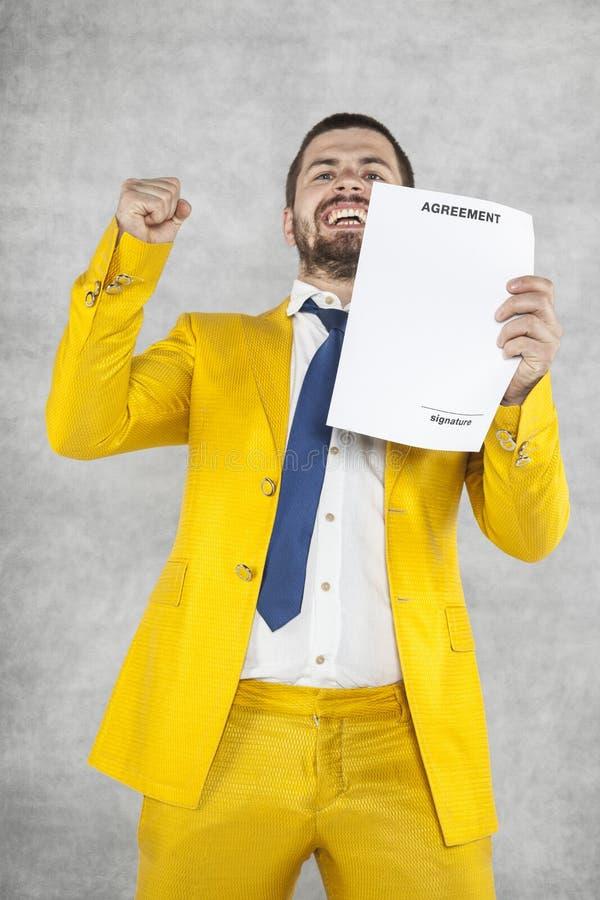De zakenman in een gouden kostuum is tevreden met het nieuwe contract stock foto