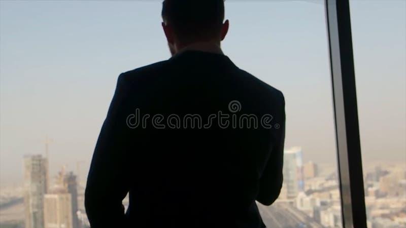 De zakenman in een kostuum kijkt uit een groot venster in een stad op een zonnige dag voorraad De mens in toevallig kostuumverbli stock afbeelding