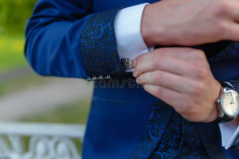De zakenman in een modieus blauw kostuum met patronen past de manchetten van zijn overhemd aan Modieuze mens in een dure kostuum  stock foto's