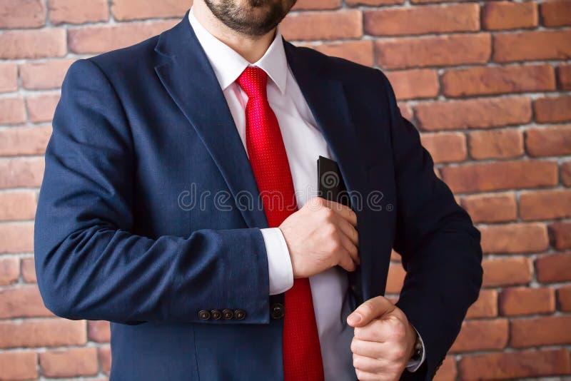 De zakenman in een rode band verbergt een beurs in zijn jasjezak stock fotografie
