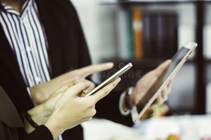 De zakenman en de bedrijfsvrouw gebruiken smartphones en tabletten die op hand met het concept gemak in online het winkelen zijn stock foto's