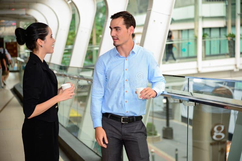 De zakenman en de onderneemster bevinden zich en bespreking over zaken met plastic mok op hand royalty-vrije stock afbeelding