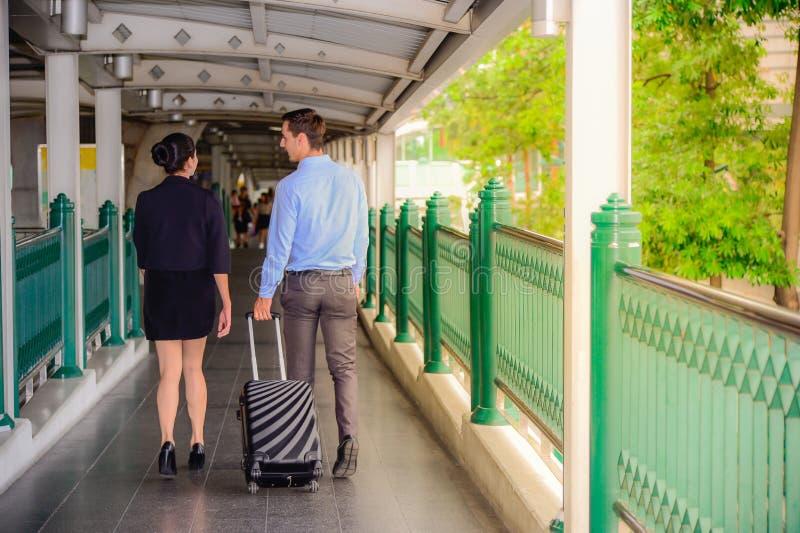 De zakenman en de onderneemster spreken en lopen samen met zwarte bagage bij de openbare straat stock foto's