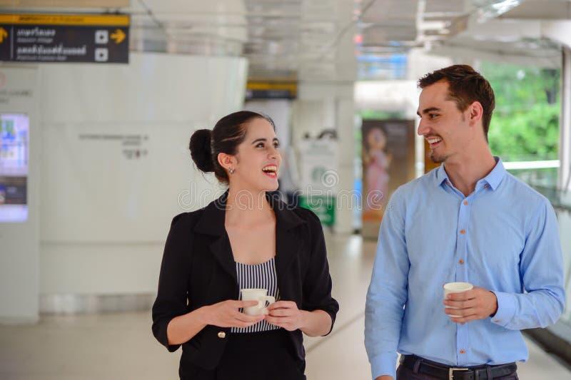 De zakenman en de onderneemster bevinden zich en lachend, bespreking over zaken met Plastic Mok op hand royalty-vrije stock afbeeldingen