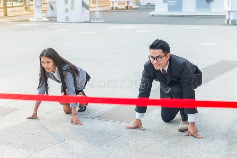 De zakenman en de onderneemster klaar om op beginpositie met verplichting aan succes te lopen stock afbeeldingen