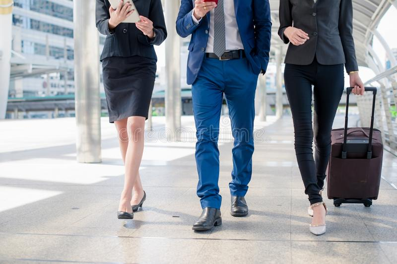 De zakenman en de onderneemster lopen samen met bagage op de openbare straat, bedrijfsreis stock foto
