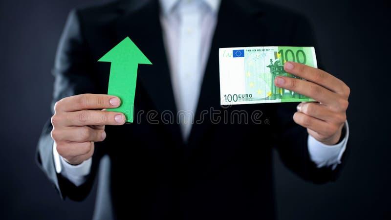 De zakenman euro bankbiljet tonen en de groene pijl die ondertekenen, munt het groeien, inkomen stock afbeelding