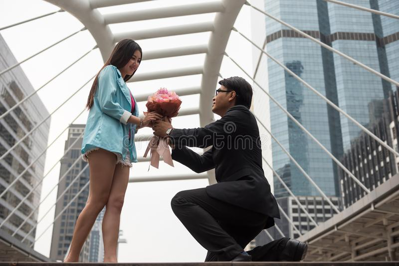 De zakenman geeft bloemboeket aan jong meisje royalty-vrije stock foto's