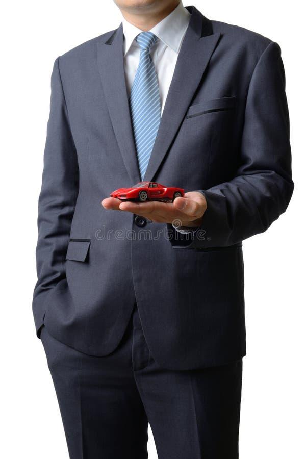 De zakenman geeft de modeldieauto aan de klant op whit wordt geïsoleerd stock foto's