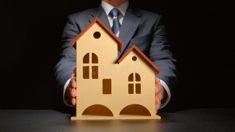 De zakenman geeft een huismodel royalty-vrije stock afbeelding