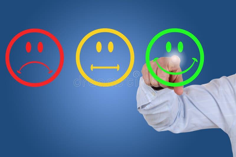 De zakenman geeft een stem voor de dienstkwaliteit met een groene smiley stock afbeeldingen