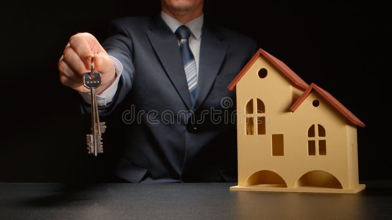 De zakenman geeft sleutels dichtbij een huismodel op een lijst royalty-vrije stock foto