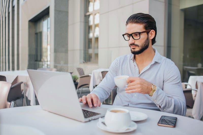 De zakenman in glazen zit bij witte lijst en werkt aan laptop Hij houdt kop van koffie in hand De kerel is ernstig en royalty-vrije stock foto's