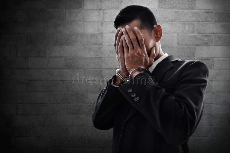 De zakenman in handcuffs behandelt zijn gezicht royalty-vrije stock foto's
