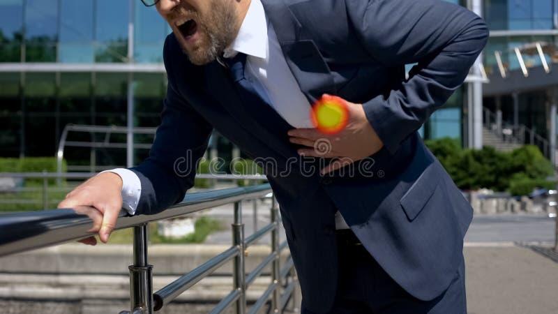 De zakenman heeft hartaanval in openlucht, wijst de vlek op pijn in borst, eerste hulp stock foto