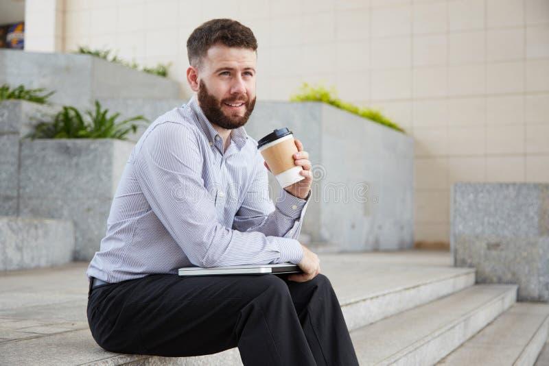 De zakenman heeft in openlucht een koffiepauze stock foto's