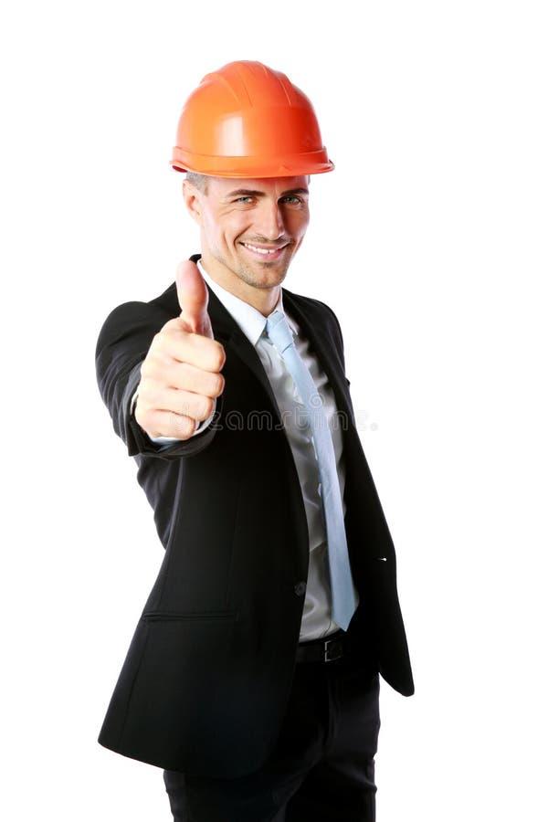 De zakenman in helm het geven beduimelt omhoog stock afbeelding