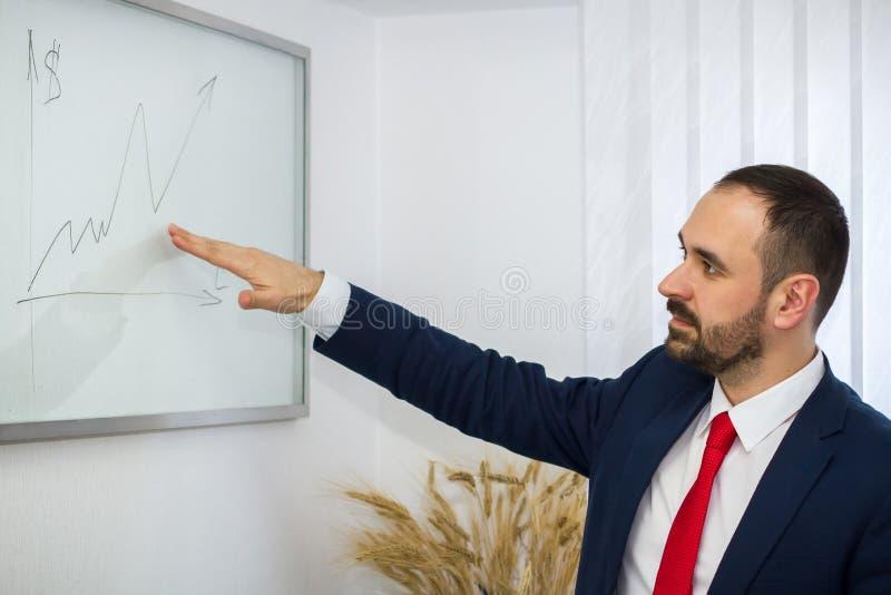 De zakenman in het bureau toont een grafiek van de winstgroei royalty-vrije stock fotografie