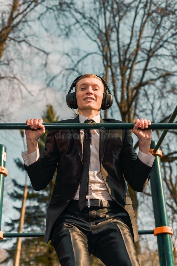 De zakenman in hoofdtelefoons heft zich op een sportenrekstok op Moderne Jonge Mens Start bedrijfsconcept royalty-vrije stock afbeeldingen