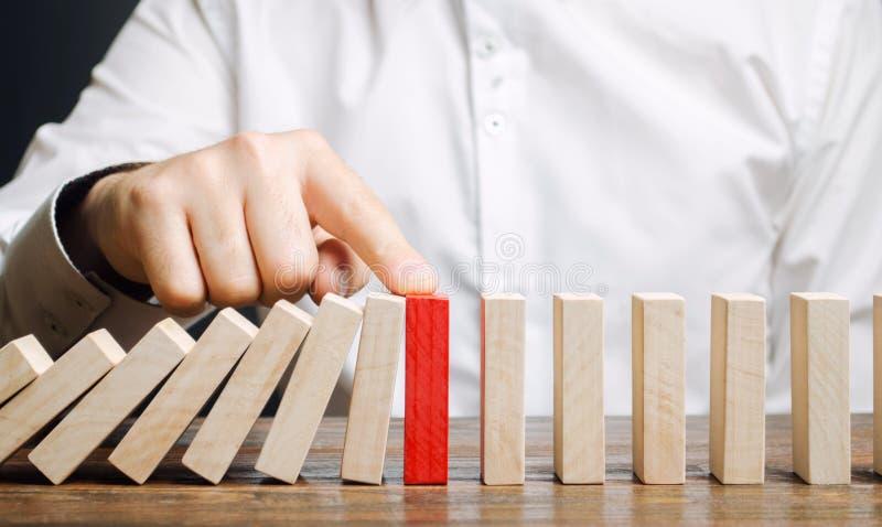 De zakenman houdt domino het vallen tegen Risicobeheerconcept Het succesvolle sterke bedrijfs en probleem oplossen Betrouwbare le stock foto