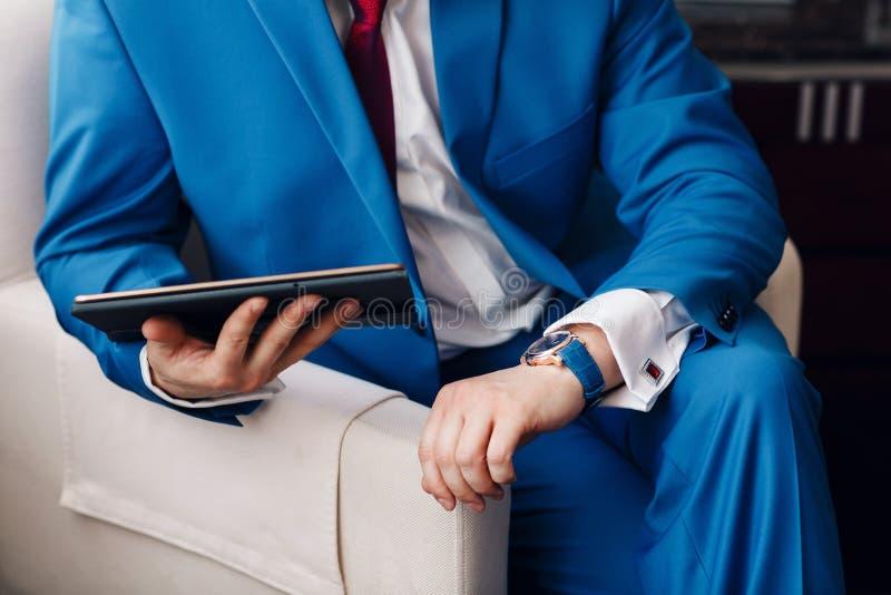 De zakenman houdt een digitale tablet in hand terwijl zitting op een bank in een blauw kostuum op hand duur mechanisch horloge royalty-vrije stock foto's