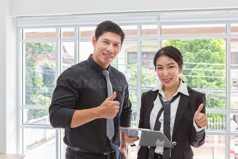 De zakenman houdt een duim De mens van zaken houdt duim tegen Het klembord van de onderneemsterholding met blad van document en p royalty-vrije stock afbeelding