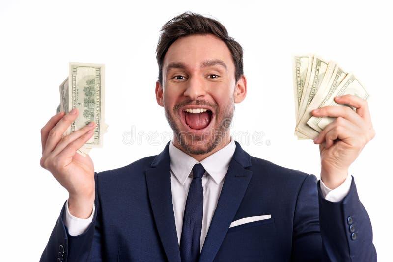 De zakenman houdt een grote die stapel dollars en glimlachen op een witte achtergrond worden geïsoleerd royalty-vrije stock afbeelding