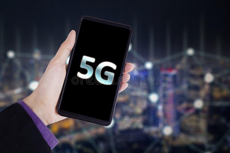 De zakenman houdt een telefoon met 5G-netwerksymbool stock afbeeldingen