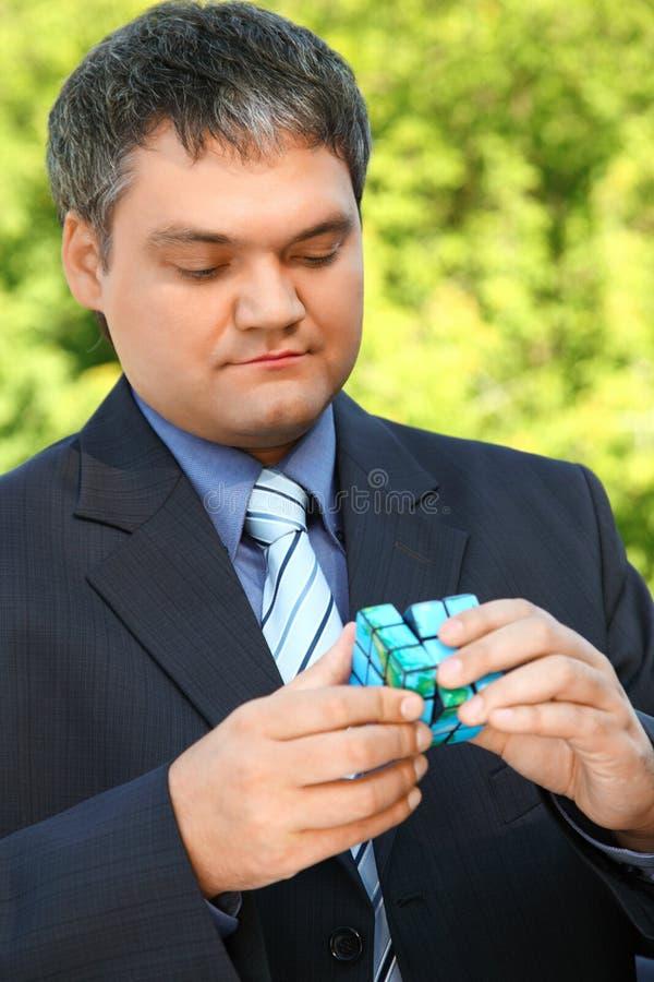 De zakenman houdt in hand kubus in de zomer openlucht royalty-vrije stock afbeelding
