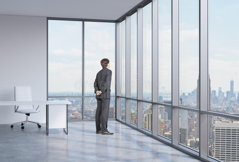 De zakenman kijkt door het hoekvenster De Achtergrond van New York royalty-vrije stock foto