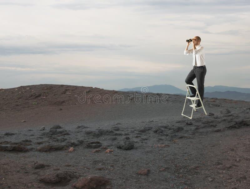 De zakenman kijkt ver voor nieuwe bedrijfskansen met een telescoop royalty-vrije stock afbeeldingen