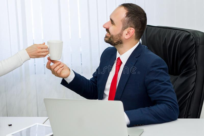 De zakenman in kostuum en rode band bekijkt klok stock afbeeldingen