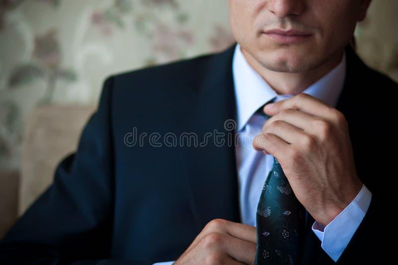 De zakenman in kostuum past zijn band aan royalty-vrije stock fotografie