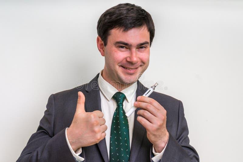 De zakenman in kostuum rookt een elektronische sigaret stock afbeelding