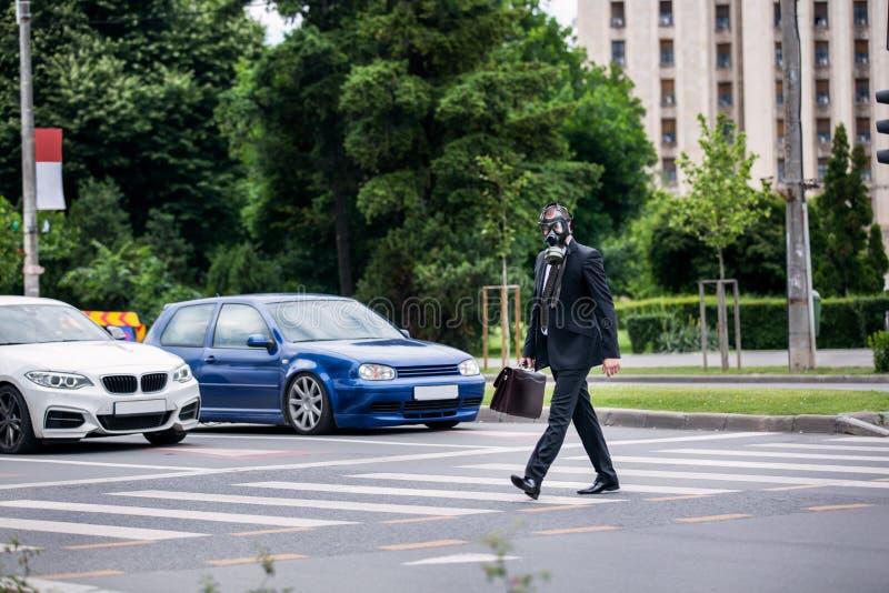 De zakenman kruist de straat openlucht met aktentas die een gasmasker dragen stock afbeeldingen