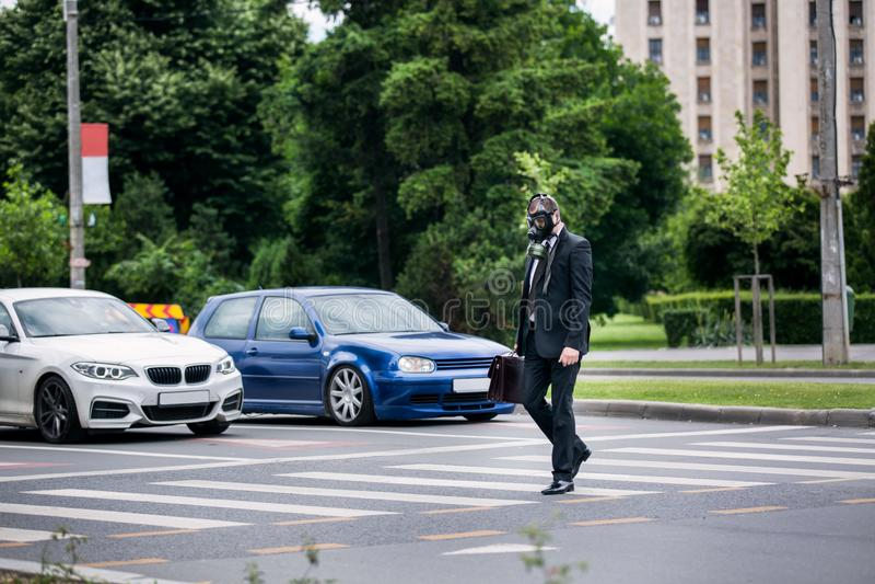 De zakenman kruist de straat openlucht met aktentas die een gasmasker op het gezicht dragen stock afbeeldingen