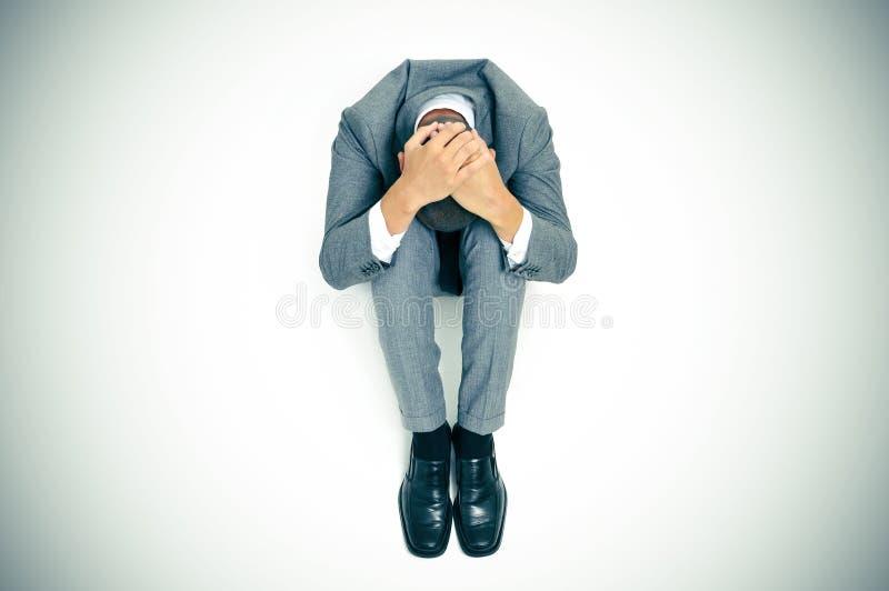 De zakenman krulde omhoog in de vloer met zijn hoofd tussen zijn kne stock afbeeldingen