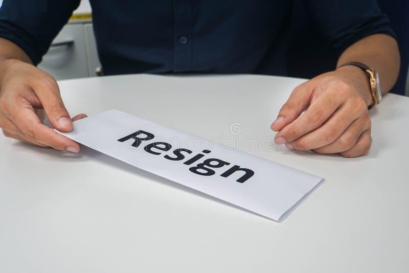 De zakenman legt berustingsbrief aan zijn werkgever voor bij bureau stock afbeeldingen