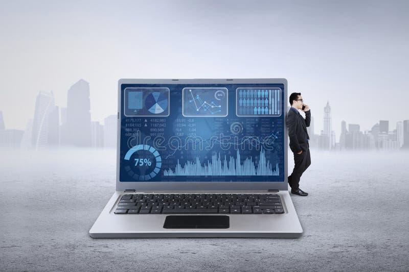 De zakenman leunt op laptop en het spreken op telefoon royalty-vrije stock afbeeldingen