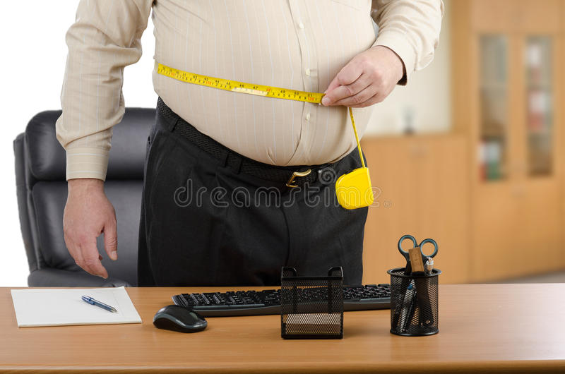 De zakenman meet zijn taille door bandmeter bij het bureau stock afbeelding