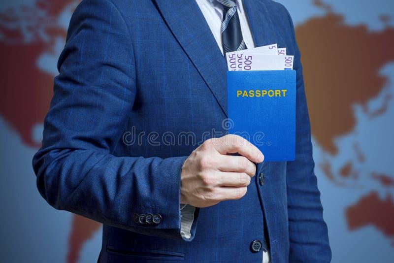 De zakenman of de mens in een kostuum houden in zijn hand een paspoort met geld Reizend concept stock foto