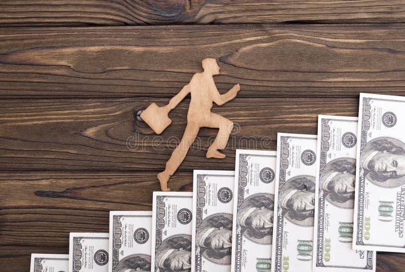 De zakenman met aktentas een beambte beklimt de treden uit dollars royalty-vrije stock afbeeldingen
