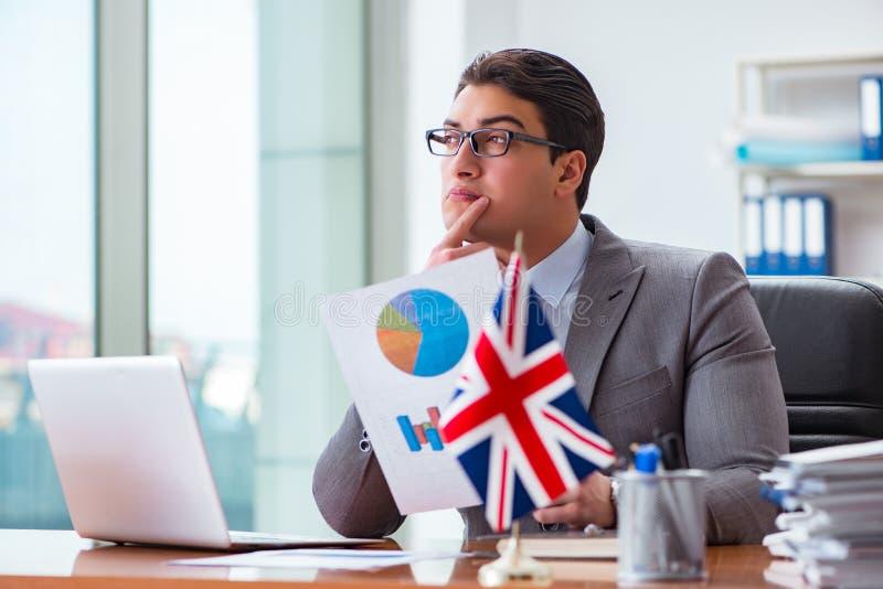 De zakenman met Britse vlag in het bureau stock foto's