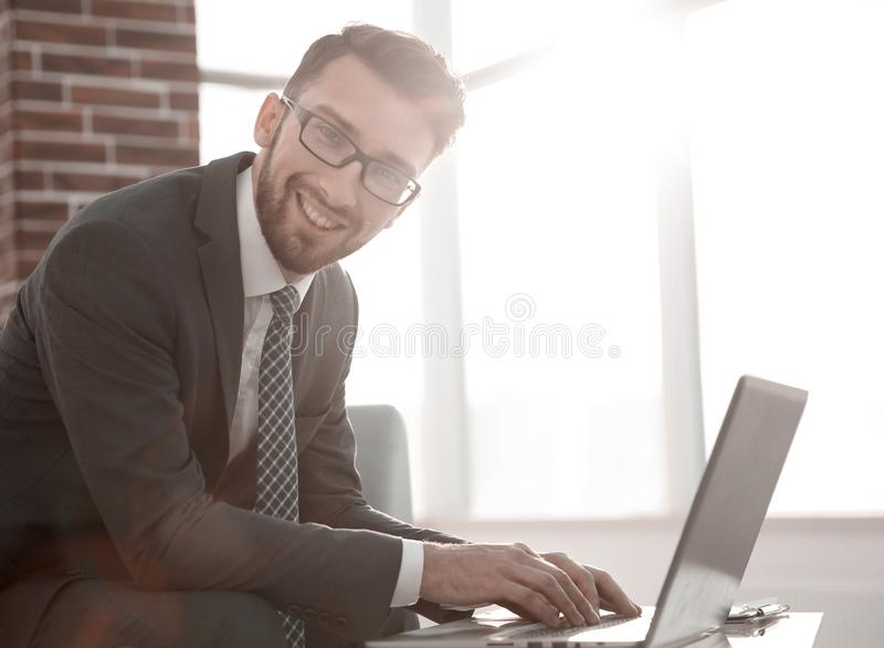 De zakenman met glazen zit bij het bureau in het bureau royalty-vrije stock fotografie