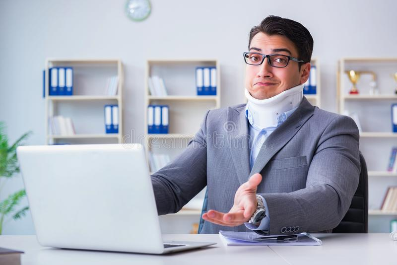 De zakenman met halsverwonding die in het bureau werken stock foto's