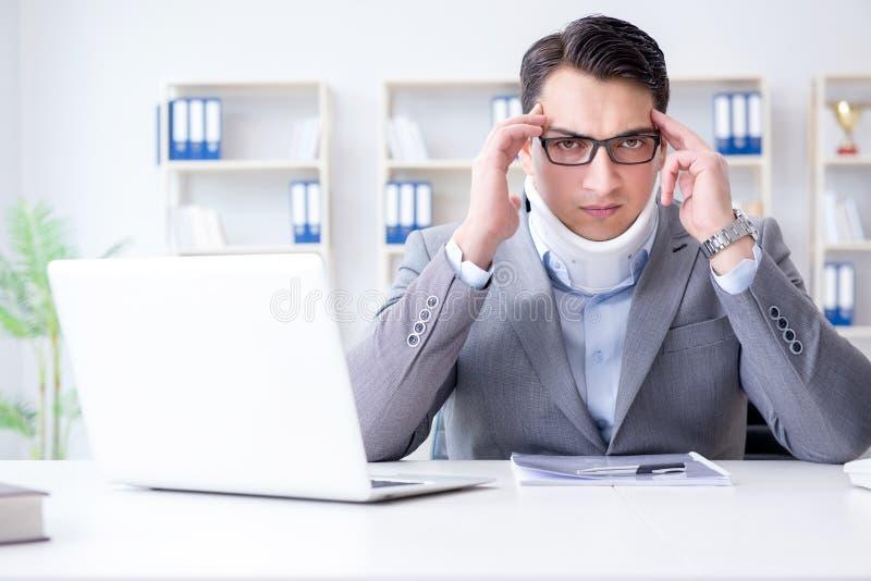 De zakenman met halsverwonding die in het bureau werken stock foto