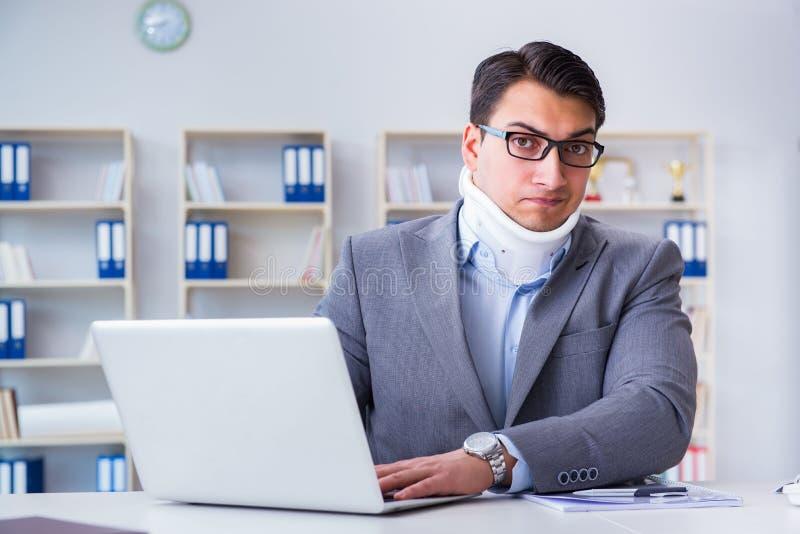 De zakenman met halsverwonding die in het bureau werken stock afbeeldingen