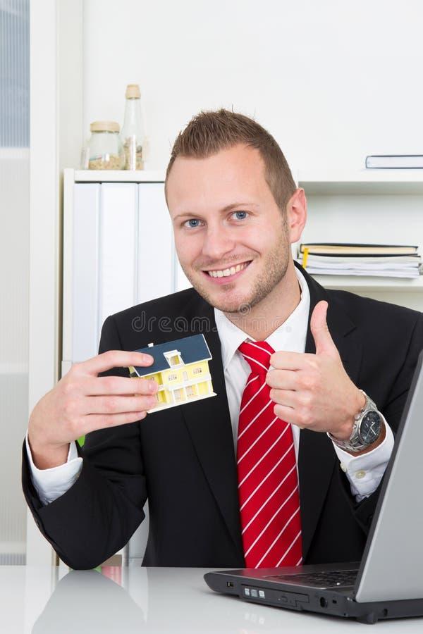 De zakenman met huis beduimelt omhoog royalty-vrije stock foto's