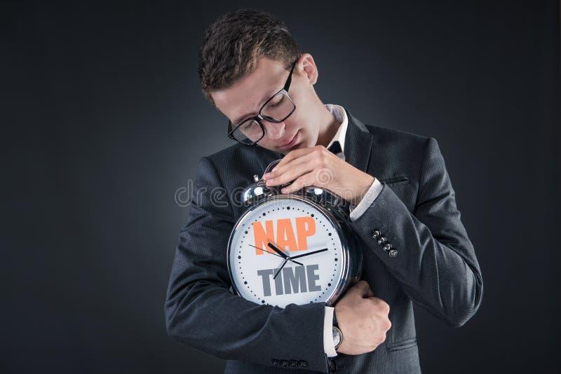 De zakenman met klokslaap in bedrijfsconcept stock foto