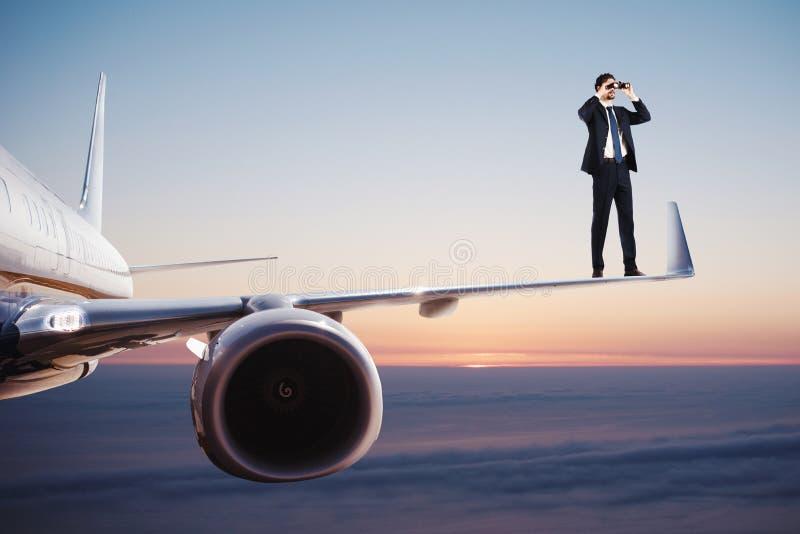 De zakenman met verrekijkers over een vliegtuig zoekt naar nieuwe bedrijfskansen royalty-vrije stock afbeelding